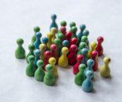Nappuloita jotka kuvaavat ihmisryhmää. Osa nappuloista on tiiviisti yhdessä, osa hieman erillään.