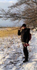 Aivovammaliiton toiminnanjohtaja Päivi Puhakka seisoo lumisella rannalla. Taustalla näkyy kaislaa ja puita.