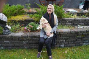 Sanna Hietanen istuu koira sylissä muurin reunalla. Taustalla näkyy erilaisia kasveja.